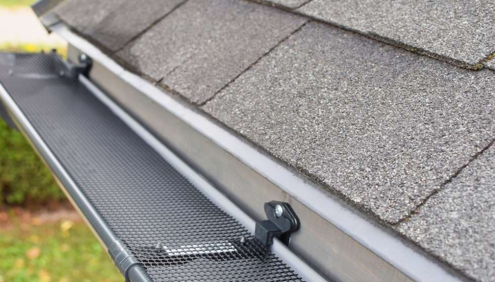 Plastic guard over new dark grey plastic rain gutter on asphalt shingles roof at shallow depth of field.