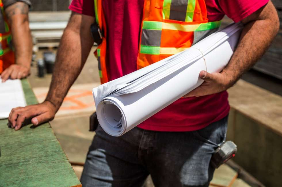 male construction worker holds rolled-up paper